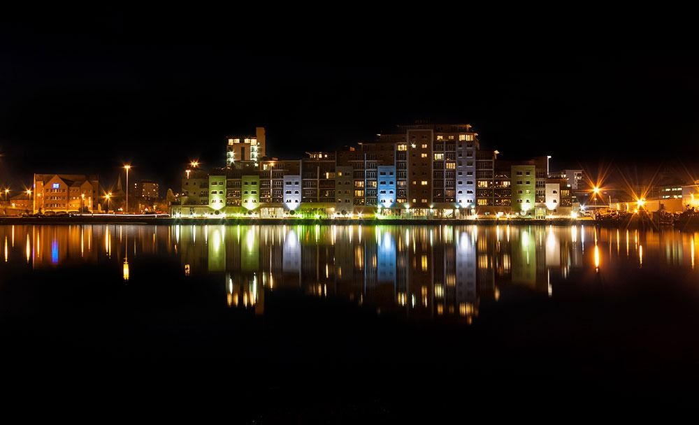 the reflection of the buildings of Poole Quay in water during night