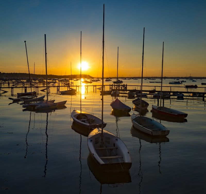 photo of multiple boats on water during sunset