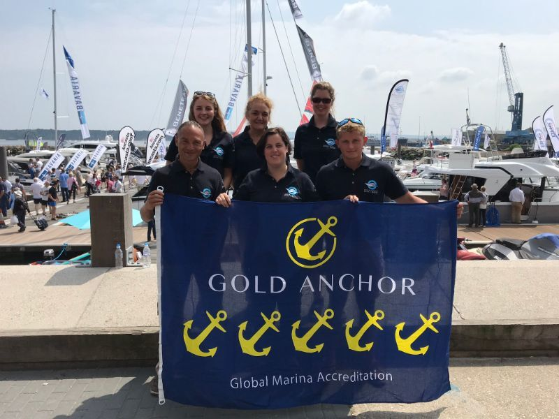 Group of people holding a Gold anchor accreditation flag