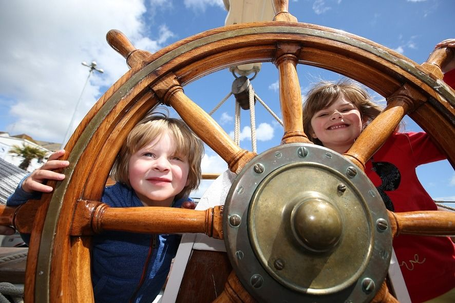 kids playing with the steering wheel on a boat